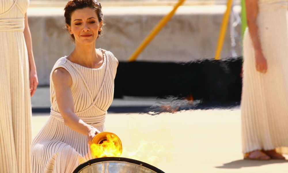 Photo: IOC: Olympic Flame lighting Ceremony in Olympia (GRE), 2014 - Katerina LEHOU, in the role of the high priestess, lighting the Olympic torch with the help of the parabolic mirror at Hera's temple.